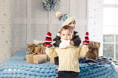 Weihnachtsniederlassung und -glocken Kinder Bruder und Schwester in der Umarmung des Hauses im Schlafzimmer nahe Bett mit Kästen, stockfotografie