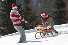 Weihnachtspaare, die mit Geschenken im Schnee spielen Stockfotografie