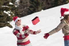 Weihnachtspaare, die mit Geschenken im Schnee spielen Lizenzfreie Stockfotos
