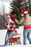 Weihnachtspaare, die mit Geschenken im Schnee spielen Stockbild