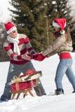 Weihnachtspaare, die mit Geschenken im Schnee spielen Lizenzfreie Stockfotografie