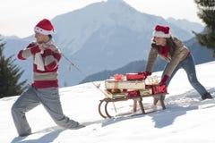Weihnachtspaare mit Schlitten und Geschenken Lizenzfreie Stockbilder