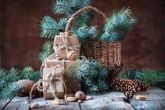 weihnachtspakete подарка на рождество Коробки, Coniferous, конусы сосны, ель, корзина, грецкие орехи, миндалины на темной деревян Стоковое Изображение