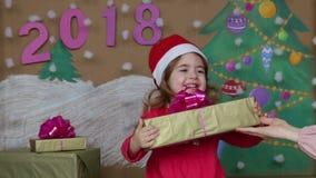 Weihnachtspakete - aanwezige Kerstmis het gelukkige nieuwe jaar van 2018 Het mamma geeft een gift aan een kleine dochter stock footage
