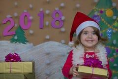 Weihnachtspakete - regalo de Navidad 2018 Felices Año Nuevo Pequeña muchacha linda que sostiene un regalo Foto de archivo