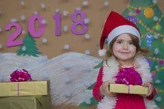 Weihnachtspakete - regalo de Navidad 2018 Felices Año Nuevo Pequeña muchacha linda que sostiene un regalo Foto de archivo libre de regalías