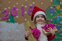 Weihnachtspakete - regalo de Navidad 2018 Felices Año Nuevo Pequeña muchacha linda que sostiene un regalo Fotografía de archivo libre de regalías