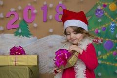 Weihnachtspakete - regalo de Navidad 2018 Felices Año Nuevo Pequeña muchacha linda que sostiene un regalo Fotos de archivo