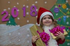 Weihnachtspakete - regalo de Navidad 2018 Felices Año Nuevo Pequeña muchacha linda que sostiene un regalo Fotografía de archivo