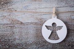 Weihnachtspapierengelsdekoration, die über hölzernem Hintergrund hängt Lizenzfreies Stockbild