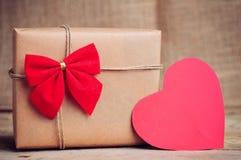 Weihnachtspapierkasten mit Herzdekoration auf Holzoberfläche Lizenzfreie Stockfotografie