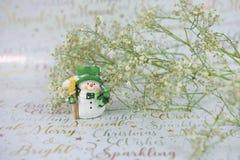 Weihnachtsphotographie von weißen grünen Blumen mit Funkeln und von nettem glücklichem Schneemann auf Weihnachtspackpapierhinterg Lizenzfreies Stockbild
