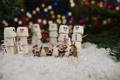 Weihnachtsphotographiebild mit Eibischen formte als Schneemann mit Zuckerglasur für das Lächeln mit Santa Claus-Dekorationen und  Lizenzfreie Stockfotografie
