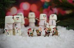 Weihnachtsphotographiebild mit Eibischen formte als Schneemann mit Zuckerglasur für das Lächeln mit Santa Claus-Dekorationen und  Stockfotografie