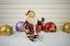 Weihnachtsphotographiebild traditioneller Santa Claus-Verzierung im Schnee mit Rot und der Goldfunkelnbaumdekorationen im Hinterg Lizenzfreie Stockfotografie