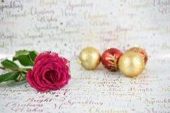 Weihnachtsphotographiebild von roten Rosen mit den Funkelnblumenblättern und rotem Goldflitter im Abstand auf Weihnachtspackpapie Stockfoto