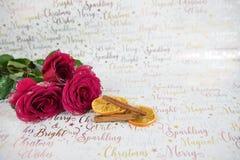 Weihnachtsphotographiebild von roten Rosen mit orange Scheiben der Funkelnblumenblätter und -Zimtstangen auf Weihnachtspackpapier lizenzfreies stockbild