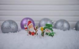 Weihnachtsphotographiebild von Santa Claus mit Schneemannverzierungen im Schnee mit Funkeln färbte Baumdekorationen im Hintergrun Stockbild