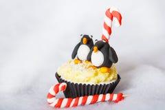 Weihnachtspinguinkleiner kuchen mit dem weißen Fondantbereifen Stockfoto