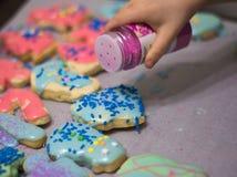 Weihnachtsplätzchen auf Tabelle mit childs Hand Stockfoto