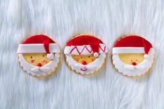Weihnachtsplätzchen mit Sankt stellen auf weißem Pelzhintergrund gegenüber Lizenzfreies Stockbild