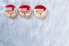 Weihnachtsplätzchen mit Sankt stellen auf weißem Pelzhintergrund gegenüber Lizenzfreies Stockfoto