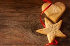 Weihnachtsplätzchen und rotes Band auf Weinleseholzhintergrund Stockfotos