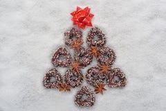 Weihnachtsplätzchenbaum gemacht durch Zimt mit einem roten Stern auf die Oberseite auf einem schneebedeckten Hintergrund Lizenzfreie Stockfotografie