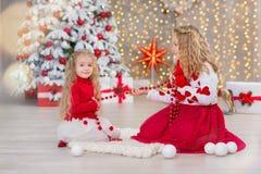 Weihnachtsporträt von zwei lächelnden Schwesterfreunden der beautyful netten Mädchen und von Weihnachtsgrünem weißem Luxusbaum im Stockfotografie