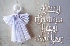 Weihnachtspostkarte mit Büttenpapierengel und -glückwunsch Bänder auf gelbem Hintergrund Lizenzfreie Stockfotografie