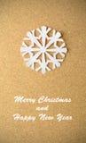 Weihnachtspostkarte mit wahrer Papierschneeflocke Stockbild