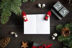 Weihnachtspostkarte mit Weihnachtsdekoration, hölzerner Kalender und leeren weißes Notizbuch Weihnachtsniederlassung und -glocken Lizenzfreies Stockbild