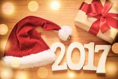 Weihnachtspräsentkarton auf hölzernem Hintergrund und Sankt-Hut Lizenzfreie Stockfotos