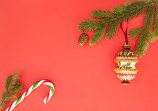 Weihnachtsrahmen auf rotem Hintergrund Grüne Tannenzweige, Weihnachtsdekoration und Zuckerstange Draufsicht, flache Lage Kopieren Stockbilder