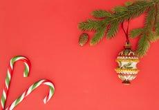 Weihnachtsrahmen auf rotem Hintergrund Grüne Tannenzweige, Weihnachtsdekoration und Zuckerstangen Draufsicht, flache Lage Kopiere Lizenzfreie Stockbilder