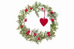 Weihnachtsrahmen gemacht von den grünen Thujazweigen, von den roten wilden rosafarbenen Früchten und von Weihnachtsbaum Dekoratio Stockfotografie