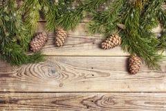 Weihnachtsrahmen gemacht von den Kiefernniederlassungen und von den Zedernkegeln auf rustikalem Lizenzfreies Stockfoto