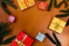 Weihnachtsrahmen gemacht von den Tannenzweigen und von den Geschenken Flache Lage Lizenzfreie Stockfotos