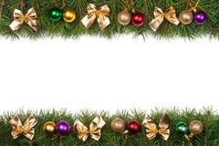 Weihnachtsrahmen gemacht von den Tannenzweigen verziert mit den Bällen und goldenen Bögen lokalisiert auf weißem Hintergrund Lizenzfreie Stockfotos