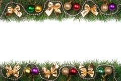 Weihnachtsrahmen gemacht von den Tannenzweigen verziert mit den Ballperlen und goldenen Bögen lokalisiert auf weißem Hintergrund Stockbilder