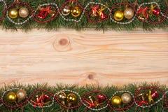 Weihnachtsrahmen gemacht von den Tannenzweigen verziert mit Glockenperlen und goldenen Bällen auf einem hellen hölzernen Hintergr Lizenzfreie Stockfotos