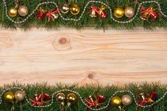 Weihnachtsrahmen gemacht von den Tannenzweigen verziert mit Glockenperlen und goldenen Bällen auf einem hellen hölzernen Hintergr Lizenzfreie Stockfotografie