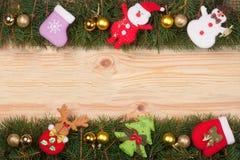 Weihnachtsrahmen gemacht von den Tannenzweigen verziert mit goldenen Bällen Schneemann und Santa Claus auf einem hellen hölzernen Stockfoto