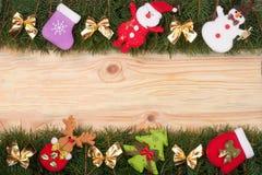 Weihnachtsrahmen gemacht von den Tannenzweigen verziert mit goldenen Bögen Schneemann und Santa Claus auf einem hellen hölzernen  Stockfotografie
