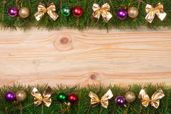 Weihnachtsrahmen gemacht von den Tannenzweigen verziert mit goldenen Bögen und Bällen auf einem hellen hölzernen Hintergrund Stockfoto