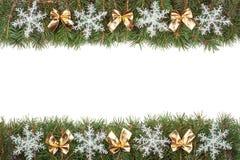 Weihnachtsrahmen gemacht von den Tannenzweigen verziert mit goldenen Bögen und von den Schneeflocken lokalisiert auf weißem Hinte Lizenzfreie Stockfotos