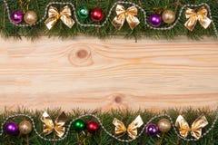 Weihnachtsrahmen gemacht von den Tannenzweigen verziert mit goldenen Bogenperlen und -bällen auf einem hellen hölzernen Hintergru Stockbild