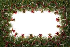 Weihnachtsrahmen gemacht von den Tannenzweigen verziert mit Perlen und von den Glocken lokalisiert auf weißem Hintergrund Stockfoto
