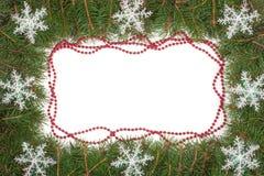 Weihnachtsrahmen gemacht von den Tannenzweigen verziert mit Perlen und von den Schneeflocken lokalisiert auf weißem Hintergrund Lizenzfreies Stockbild