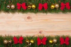 Weihnachtsrahmen gemacht von den Tannenzweigen verziert mit Rotbögen und goldenen Bällen auf einem hellen hölzernen Hintergrund Stockbilder